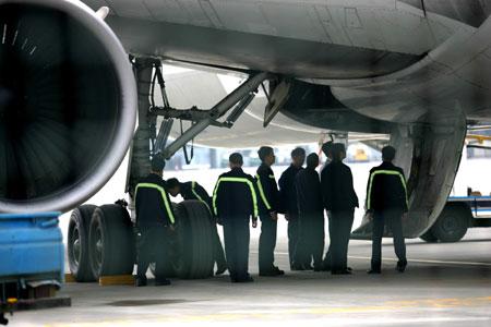 飞机刚入机位,多名工作人员围着右起落架