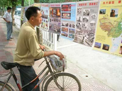 市民在湄潭县城观看国防教育宣传画-湄潭开展国防教育宣传活动 图